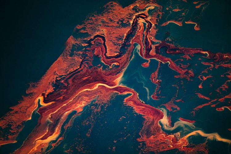 Iperoggetti sono anche le perdite di greggio: in questo caso una foto ritrae il disastro della Deepwater Horizon nel 2010. Fossile poliedrico che abbiamo sottratto alla Terra per farne una costante della nostra vita, il petrolio è una sorta di macchina del tempo che diventa risorsa. Gli iperoggetti sono potentemente estetici: creano o alterano canoni visivi. Il disastro ambientale è un ponte tra carte marmorizzate, glitch e biologia. È fuori e dentro di noi. Copyright: Daniel Beltrà.